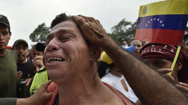 Un venezolano reacciona mientras se despide de un pariente, miembro de las Fuerzas Armadas Nacionales Bolivarianas de Venezuela (FANB) mientras es escoltado por agentes de la policía colombiana después de desertar, cerca del puente internacional Simón Bolívar en Cúcuta, | Fuente: AFP